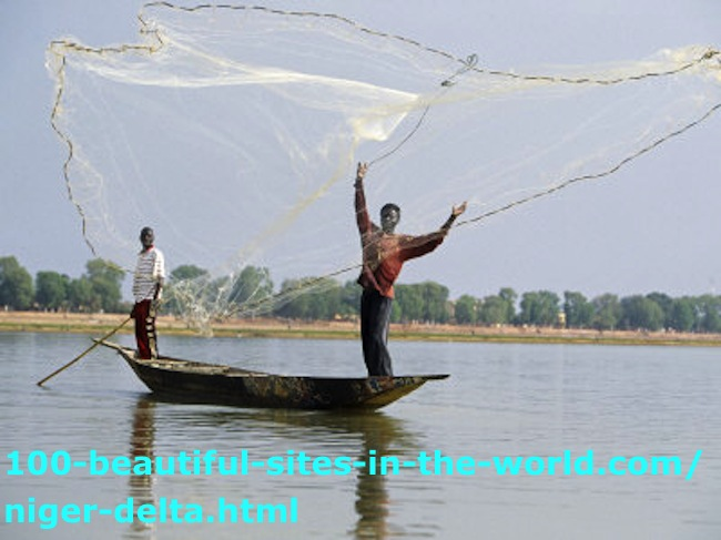 The Niger Delta: A Fisherman with His Colleague on a Boat Casting his Net.